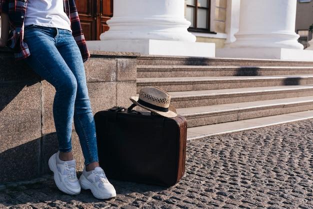 Sección baja de mujer recostada en la pared cerca de su bolsa de equipaje y sombrero