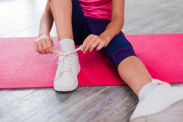Sección baja de una niña sentada sobre una colchoneta de ejercicios que ata un cordón