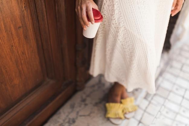 Sección baja de una niña con taza de café para llevar