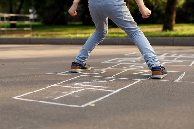 Sección baja de niño jugando hop-scotch en el patio de recreo. rayuela popular juego callejero.