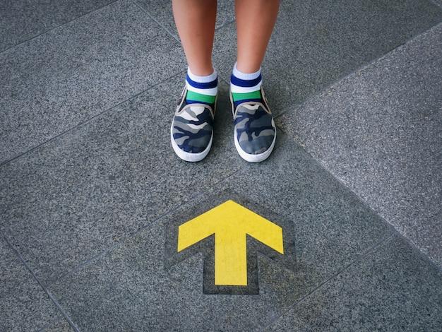 Sección baja del niño de pie delante de la flecha direccional amarilla