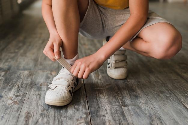 Sección baja de un niño que pone la correa del zapato en el piso de madera dura
