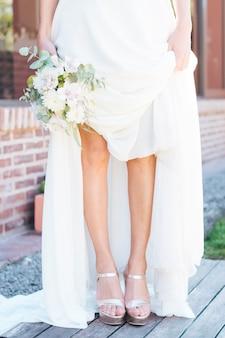 Sección baja de una novia con un ramo de flores en la mano, mostrando sus tacones de moda