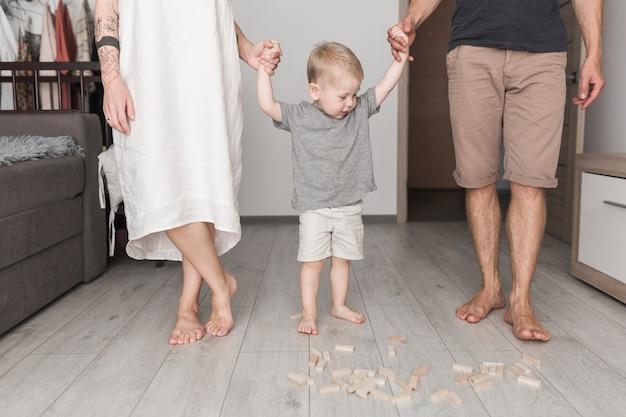 Sección baja de los padres sosteniendo la mano de su hijo en casa.
