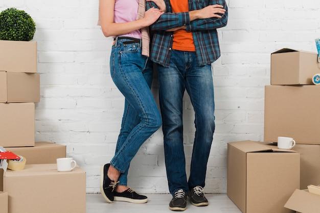 Sección baja de la pareja de pie entre las cajas de cartón con dos tazas.