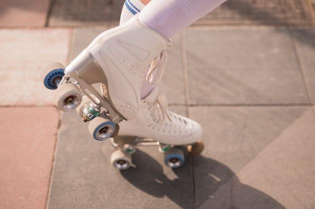 Sección baja de patinador femenino con patín blanco vintage.