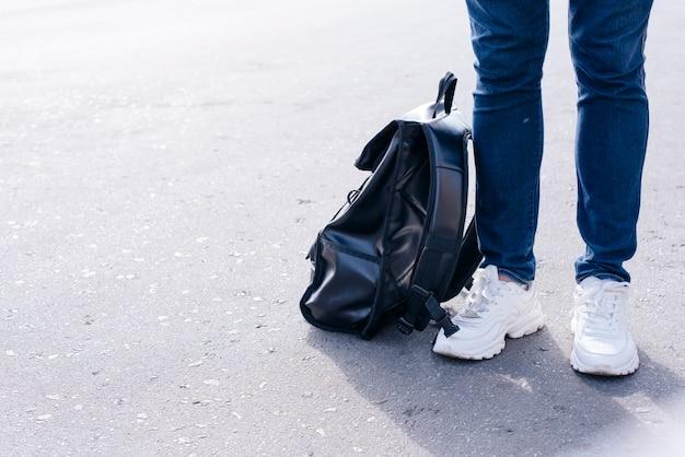 Sección baja de una persona parada en la calle con mochila negra.