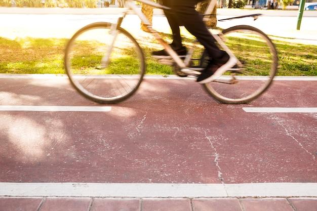 Sección baja de una persona que monta la bicicleta en el parque.