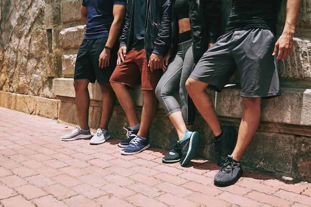 Sección baja de personas irreconocibles en ropa deportiva de pie en la pared de un edificio