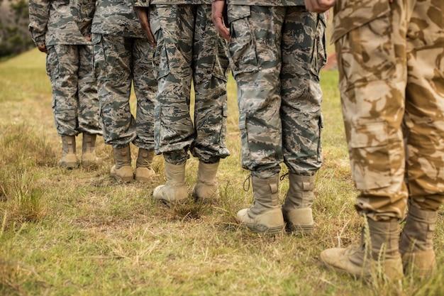 Sección baja de soldados militares haciendo fila