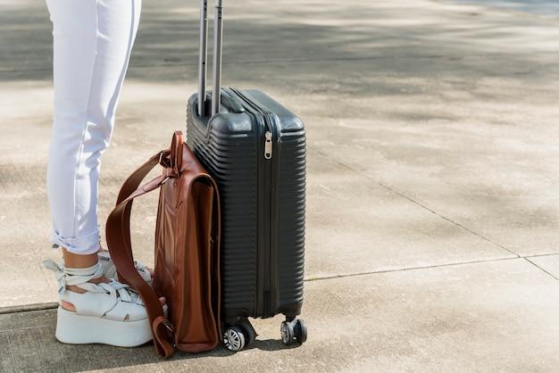 Sección baja de turista femenina de pie en la carretera con equipaje y bolsa de cuero