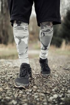 Sección baja de zapatos de corredor masculino en el camino de grava