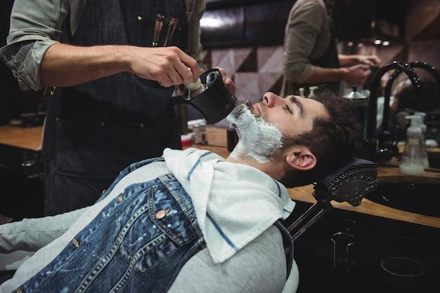 Sección intermedia de barbero aplicando crema en la barba de los clientes