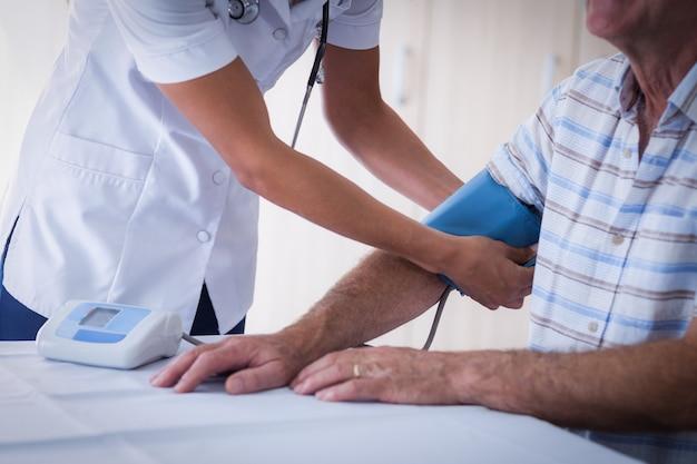 Sección intermedia de doctora comprobando la presión arterial del hombre mayor