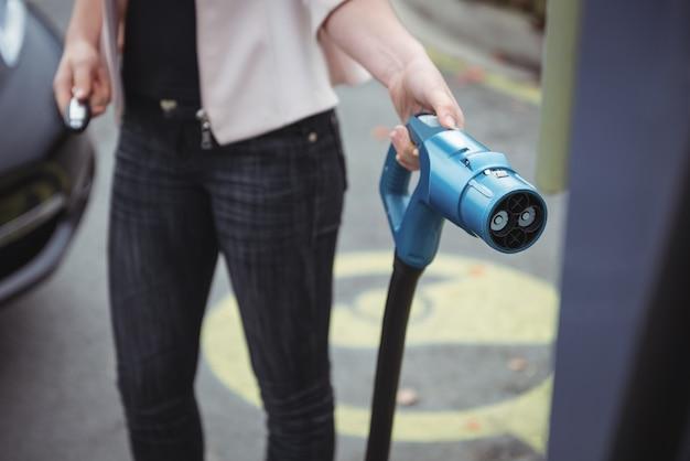 Sección intermedia de mujer cargando coche eléctrico