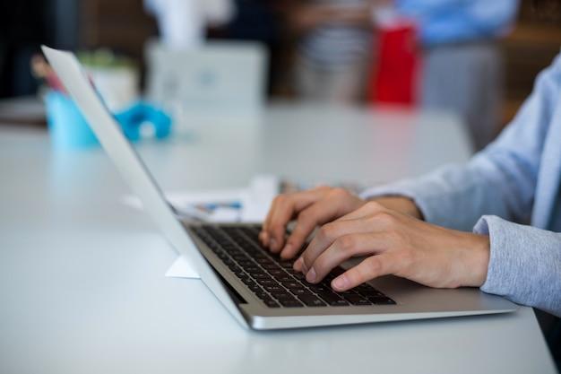 Sección intermedia de mujer ejecutiva de negocios usando laptop