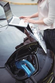 Sección intermedia de mujer con portátil mientras carga un coche eléctrico