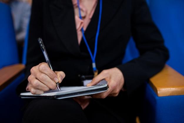 Sección intermedia de mujeres ejecutivas de negocios que participan en una reunión de negocios