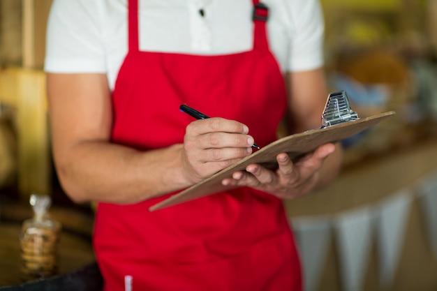 Sección intermedia del personal de la panadería escribiendo en el portapapeles en el mostrador