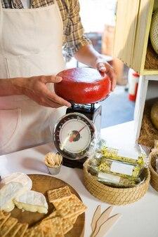 Sección intermedia del personal pesando queso gouda en el mostrador
