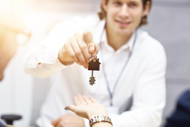 Sección media del agente inmobiliario y las manos del comprador con llaves en la oficina
