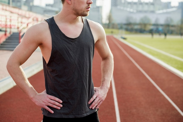 Sección media de un atleta masculino de pie en la pista de carreras
