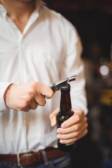 Sección media del barman abriendo una botella de cerveza