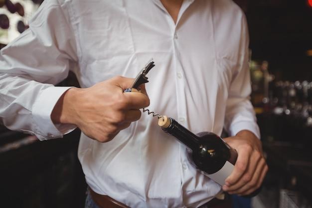 Sección media del barman abriendo una botella de vino