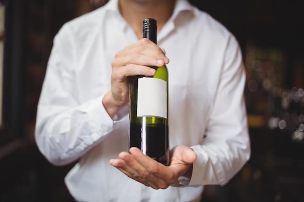 Sección media del barman sosteniendo una botella de vino