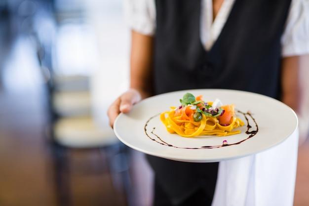 Sección media de camarera con plato