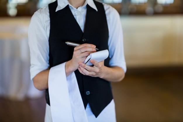 Sección media de camarera tomando orden