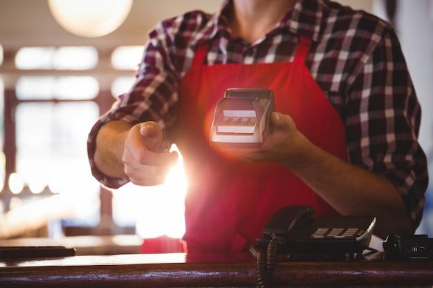 Sección media del camarero que muestra la máquina de tarjeta de crédito