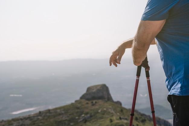 Sección media del caminante masculino sosteniendo bastones de senderismo en lo alto de la montaña
