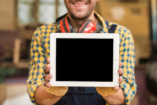 Sección media de un carpintero mostrando tableta digital con pantalla en blanco