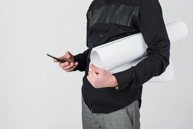 Sección media de un arquitecto masculino que sostiene el modelo usando el teléfono móvil