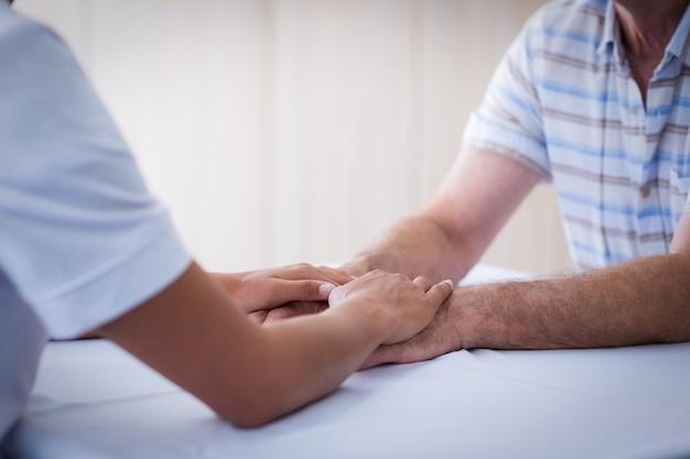 Sección media de doctora consolando a hombre senior en la sala de estar