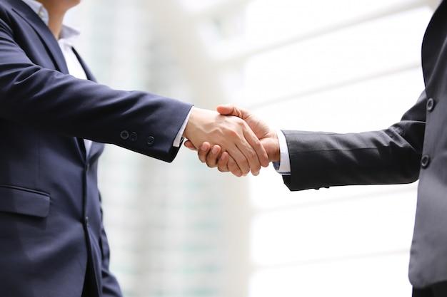 Sección media de dos hombres de negocios dándose la mano al aire libre