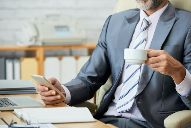 Sección media de un empleado de aspecto profesional tomando café y navegando por la red en un teléfono inteligente