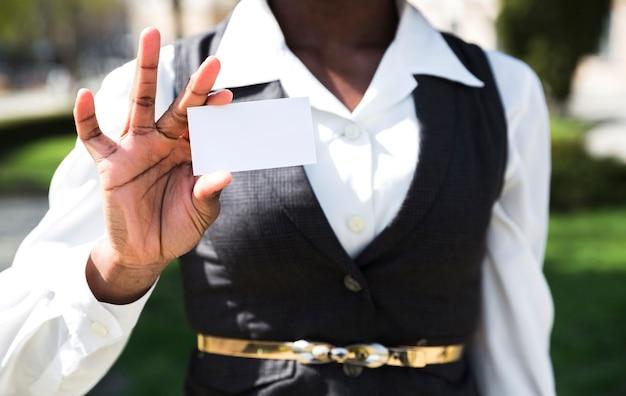 Sección media de una empresaria mostrando tarjeta de visita blanca