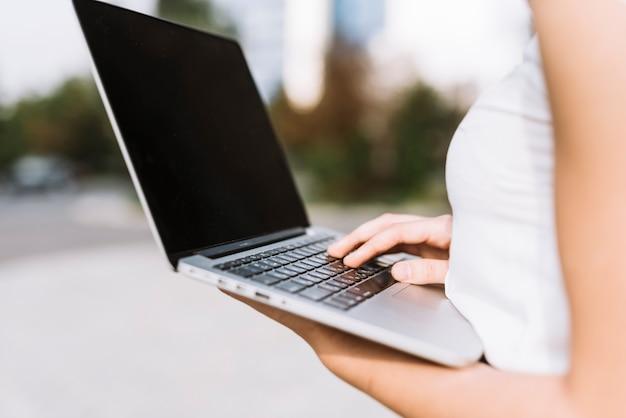 Sección media de empresaria usando laptop sosteniendo en la mano