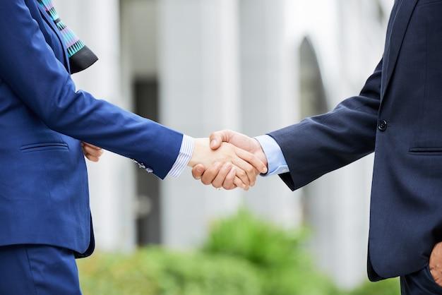 Sección media de empresarios dándose la mano al aire libre