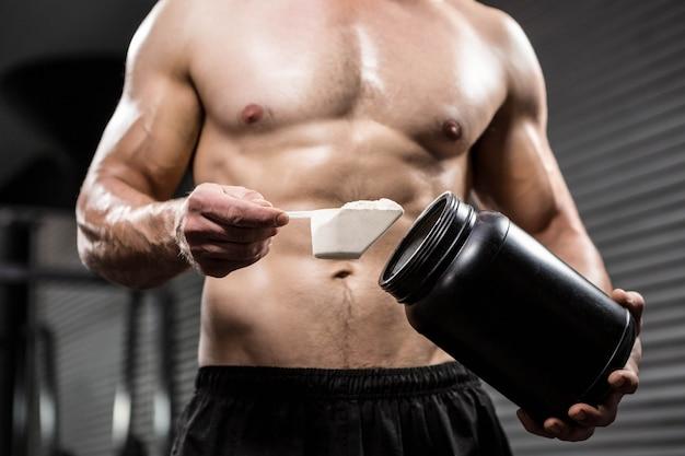Sección media del hombre sin camisa tomando proteínas de lata en el gimnasio de crossfit