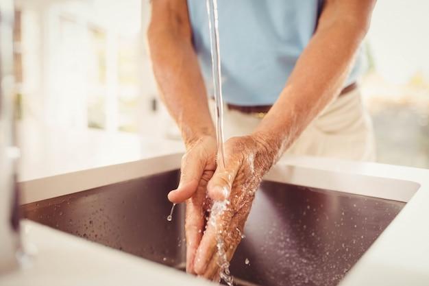 Sección media del hombre mayor que se lava las manos en la cocina