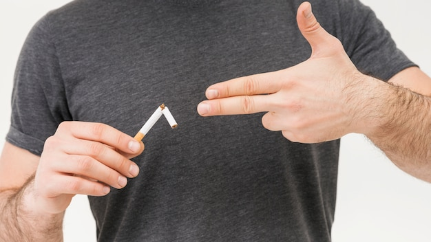 Sección media de un hombre muestra el gesto de la pistola hacia el cigarrillo roto.
