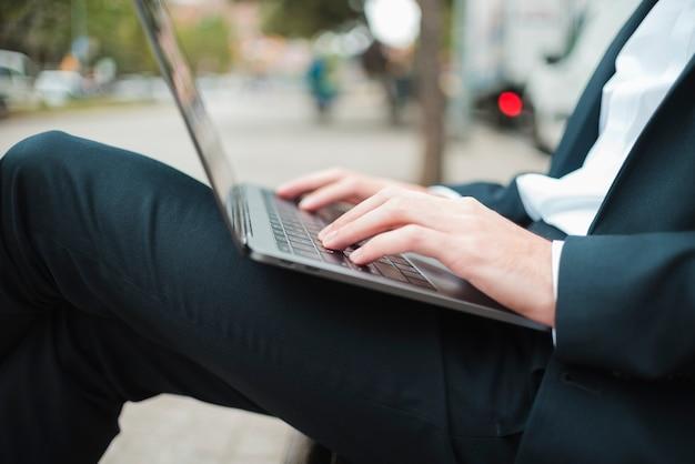Sección media de un hombre de negocios escribiendo en la computadora portátil