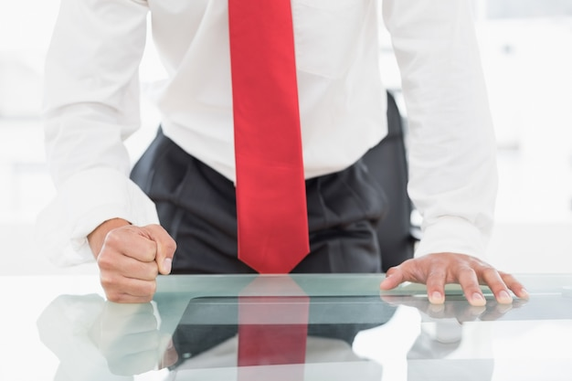 Sección media de un hombre de negocios con el puño cerrado en el escritorio