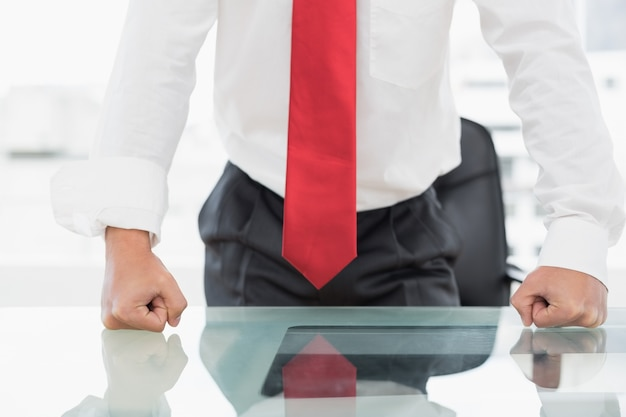 Sección media de un hombre de negocios con los puños apretados en el escritorio
