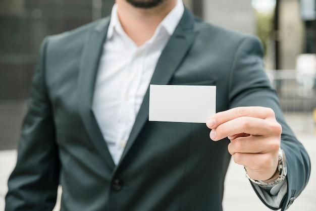 Sección media de un hombre de negocios que muestra la tarjeta en blanco blanca