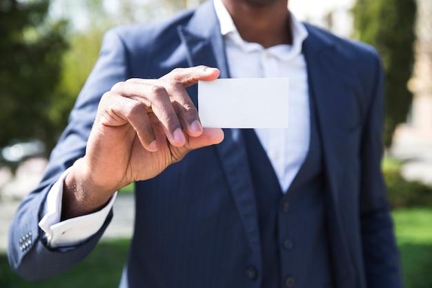 Sección media de un hombre de negocios que muestra la tarjeta de visita blanca