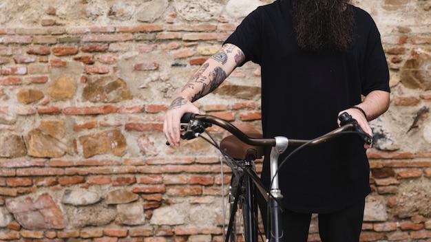 Sección media de un hombre de pie con bicicleta contra la pared